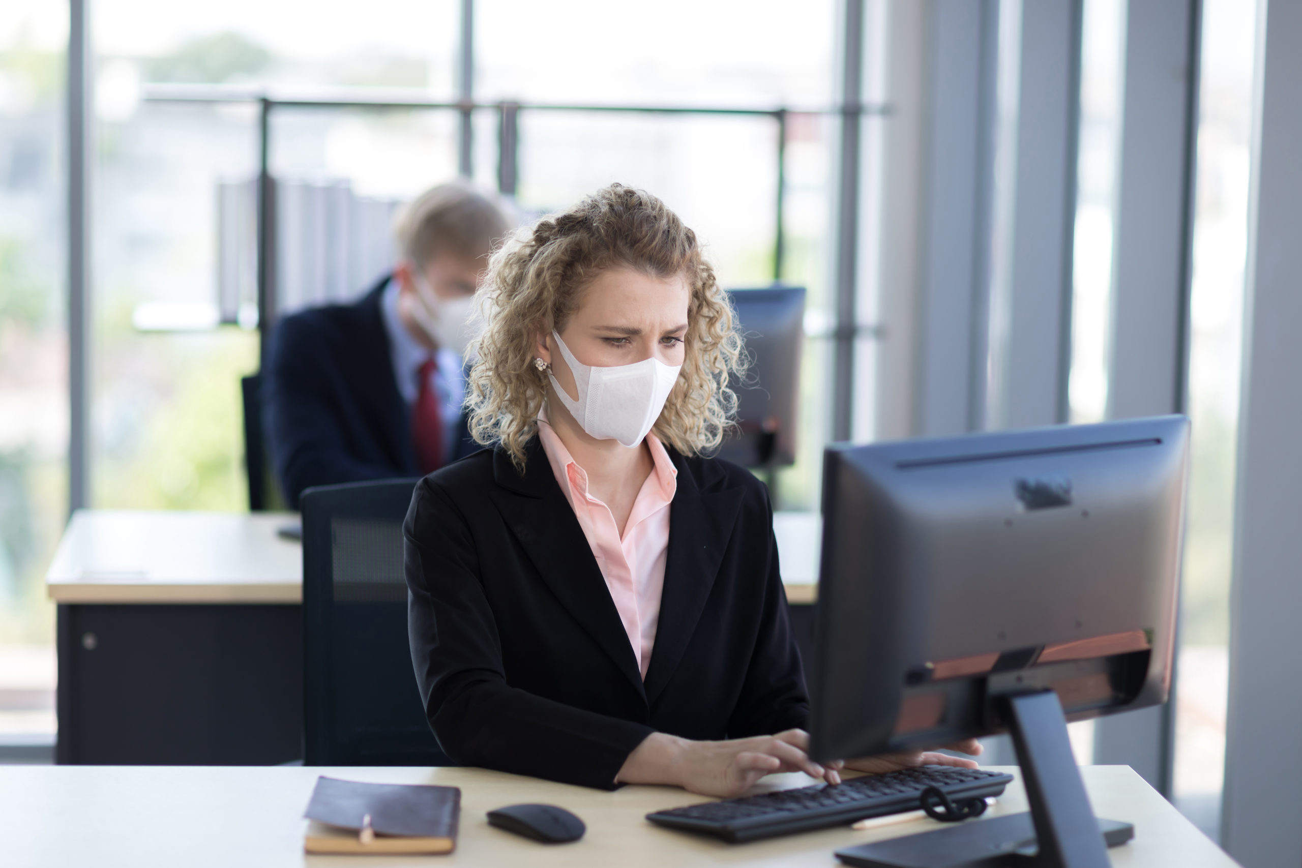 this is a photo of a woman working at a computer in an office wearing a protective face mask